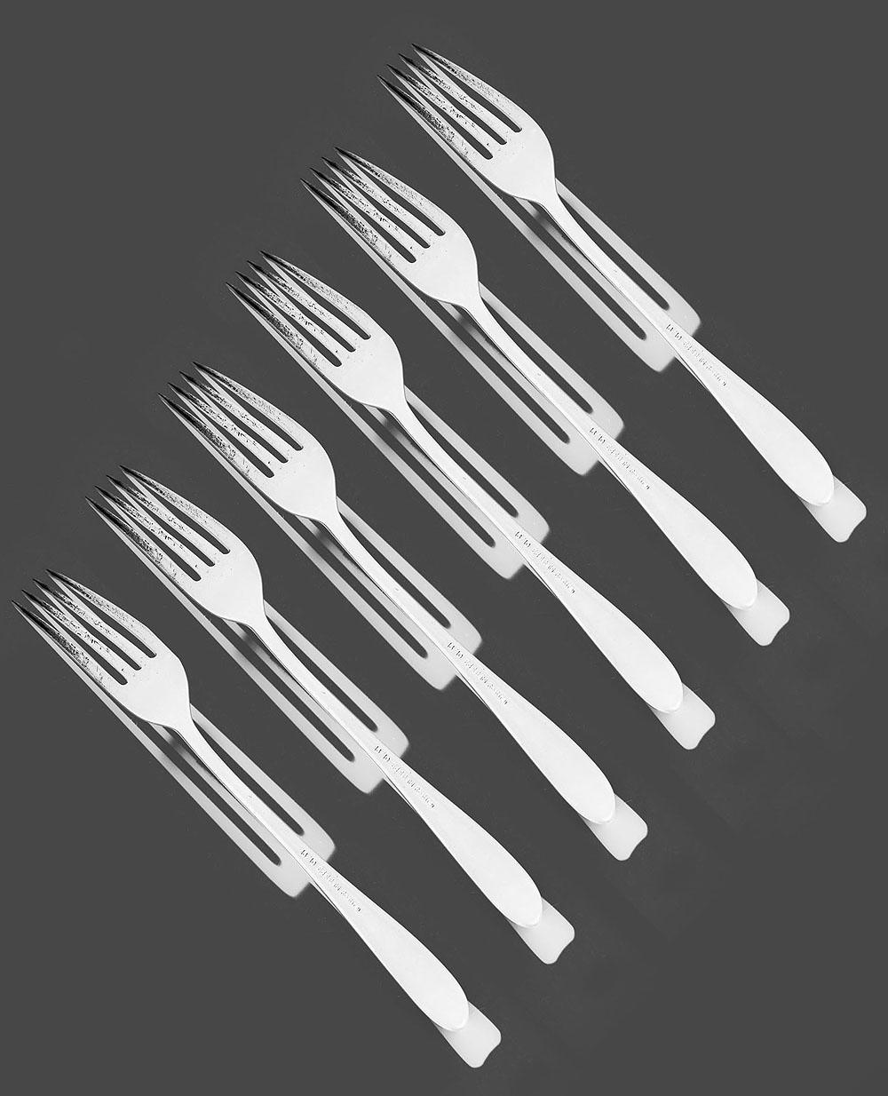 De zon schijnt fel op de tafel waar een vork ligt. Dat geeft verrassende schaduwen die steeds veranderen.